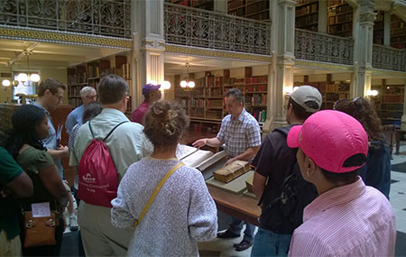Paul Espinosa of the Peadbody Library shows Literary Mount Vernon Walking Tour participants a rare book inside Peabody Library.