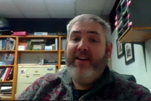 Garrett Lakes Arts Festival Board Chairman Andrew Harvey in a video screen shot. We she his face, gray hair, gray beard and mustache. He is wearing a maroon and gray sweater over a black t-shirt. In the background, we see file cabinets and supplies.