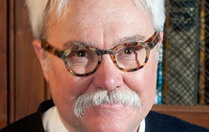 Bill Peak: a white man with white hair and a white mustache, with thick, tortoise-shell glasses.