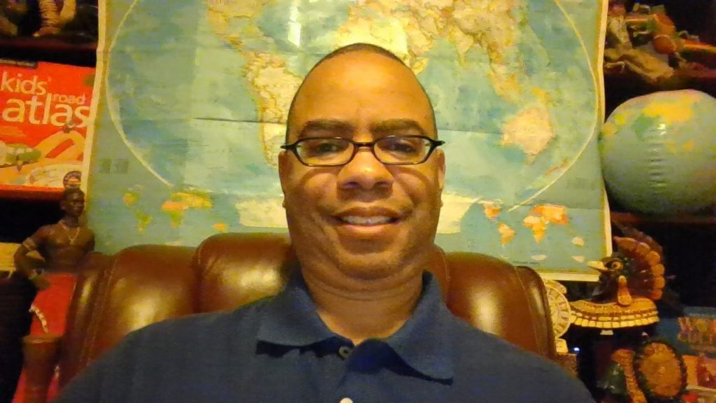 "Dr. Jermaine Ellerbe, a lighter-skinned Black man, with glasses and a closely-shaved hair cut, wears a navy blue polo. He sits on a leather chair in front of a world map. Next to the map on the right, is a blow-up globe. On the map's left, is a red box that says ""Kids' Road Atlas."""