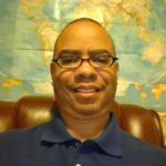 """Dr. Jermaine Ellerbe, a lighter-skinned Black man, with glasses and a closely-shaved hair cut, wears a navy blue polo. He sits on a leather chair in front of a world map. Next to the map on the right, is a blow-up globe. On the map's left, is a red box that says """"Kids' Road Atlas."""""""