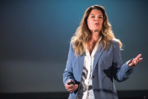 A white woman speaking in front of a blue background. She has very light brown hair and wears a white button-down shirt and a light blue blazer.