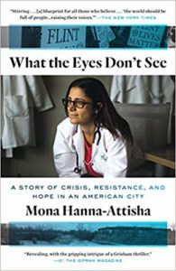 Cover ofWHAT THE EYES DON'T SEE: A STORY OF CRISIS, RESISTANCE, AND HOPE IN AN AMERICAN CITY by Mona Hanna-Attisha. The cover features Dr. Hanna-Attisha in a white doctor's coat looking left.  Above the title and protest signs about the Flint water crisis shaded in blue.