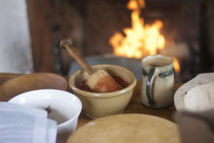 A tan, ceramic mortar and wooden pestle on a wooden table surrounded by other bowls. The table is in front of a fireplace with a fire.