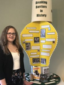 """A brunette, white teenager with brown hair and glasses in a black sweater, white tank top, and black patterned skirt. She is next to her project. It is made out of yellow poster board with text and images. The title of the poster says """"Breaking Barriers in History."""""""