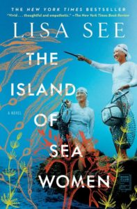 The book cover of THE ISLE OF SEA WOMEN by Lisa See. The cover is aqua with white font. Two Korean women stand in clothes, swimcaps, and goggles. They are carrying nets. They stand on a rock near the water. We also see plants.