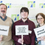 A 2018 Letters About Literature State Finalist is posing for a picture with his two family members holding congratulatory signs in front of the Maryland Humanities step-and-repeat sign.