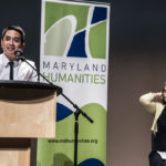 The 2018 LAL Keynote Speaker, author Minh Lê, addresses the audience during his speech, while Dr. Phoebe Stein, Executive Director of Maryland Humanities watches from the stage.