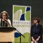Dr. Phoebe Stein (Executive Director, Maryland Humanities), begins to read the names of the 2018 LAL State Finalists, while Becky Brasington Clark, Director of Publishing, Library of Congress, watches from the stage.