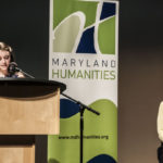 2018 LAL Level 1 State Winner Lucy Virgilio reads her winning letter to the audience, while Dr. Phoebe Stein, Executive Director of Maryland Humanities listens.