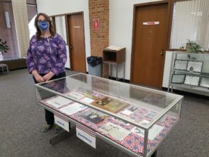 Yelizaveta L Zakharova, a white woman with layered brown hair, stands in a library to the left of an exhibit case. She wears a patterned purple shirt and black slacks. Next to her, an exhibit case displays pictures and documents of and about John H. Bambacus.