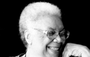 a Black and white photograph of Lucille Clifton from the chin up, in front of a black background. The photo is later in life and she is wearing glasses and laughing. Her hand rests near her chin.
