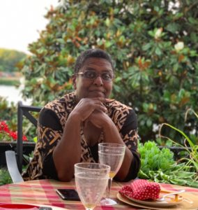A Black woman with short hair sits behind a table covered in red checkered tablecloth and empty drink glasses. She sits in front of a tree with water in view behind her.