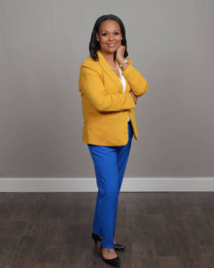 A Black woman standing on a wooden floor wearing a yellow blazer and royal blue pants.