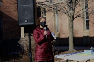 Congresswoman Odette Ramos in a burgundy winter coat standing with a microphone, wearing a mask. She stands outside in front of a speaker, with a tree in view.