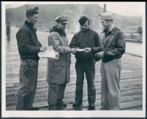 A black and white image of four World War II Coast Guardsmen and soldiers receive their voting applications while stationed in the Aleutian Islands. To their left, a man in the background looks on behind them. To their right, there is an airplane.