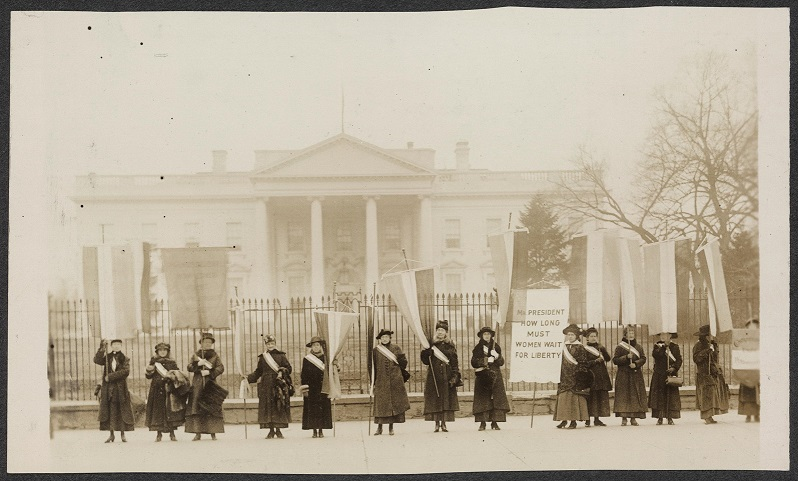 A 1917 black and white photograph of 13 white suffragettes in dark coats and sashes in front of the White House. Some have picket signs.