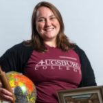 """Laya Theberge, a white woman with light brown hair, wears a maroon t-shirt with """"Augsburg College"""" on it and a black cardigan. She holds a globe and rolling pin in one hand an a framed painting in the other (the painting itself is not visible)."""
