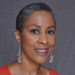 A Black woman with short, cropped hair wears dangly, silver earrings with orange stones. She wears and orange shirt. The image goes to the top of her shoulders.