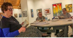 Three white adults, middle-aged to older, sit at a round table looking at their books. There is artwork of nature on the walls.