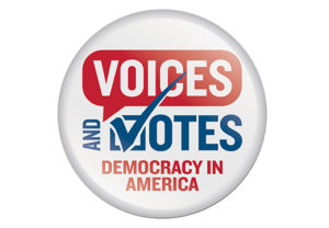 """A white round button that looks like a campaign button says """"Voices and Votes: Democracy in America."""" Every letter is capitalized. """"Voices"""" is in white font on a red speech bubble and """"Democracy in America"""" are in red font. """"And Votes"""" is in blue font. The """"V"""" is also a checkmark."""