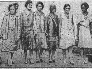 A 1930 stylized image of 7 Black women in skirts and dresses a little lower than the knee, in various shades and low heels. The third from the right wears a hat. The image looks to be candid and some women are smiling slightly. Estelle Hall is third from the right and August Chessell is third from the left.