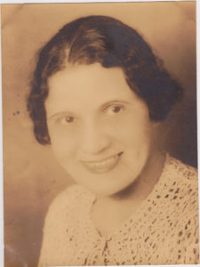 August Chissell in an old black-and-white photograph of her head and shoulders. She is a lighter-skinned Black woman with dark black hair. She smiles and looks to be wearing a cardigan. Due to the picture's age, it looks more light brown and black, than black and white.
